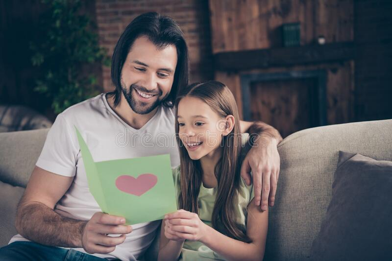 Photo of little adorable funny lady her handsome daddy sit cozy sofa hugging hold cute card birthday present reading. Photo of little adorable funny lady her stock photos