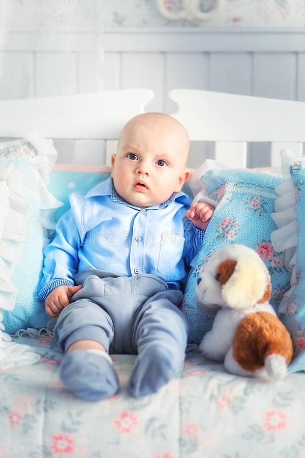 Little boy in blue clothes sitting on the sofa. Photo of Little boy in blue clothes sitting on the sofa royalty free stock photography