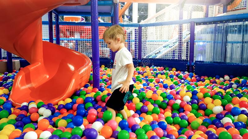 Photo of little boy playing in the pool full of colroful plastic balls. Toddler having fun on playground in shopping stock photo