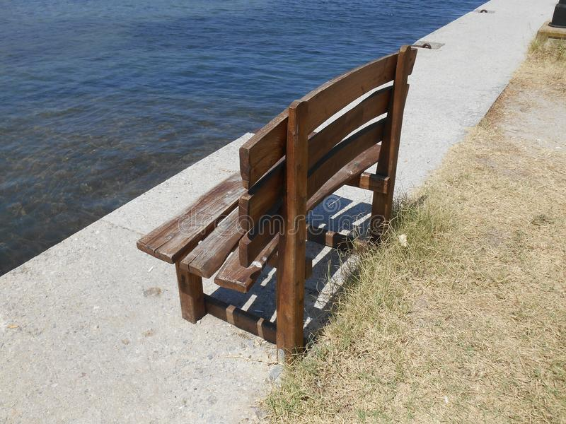 Wooden brown bench by the sea on promenade. Photo of little brown bench by the bright blue sea on promenade, sunny summer day in Stavros, Greece stock image