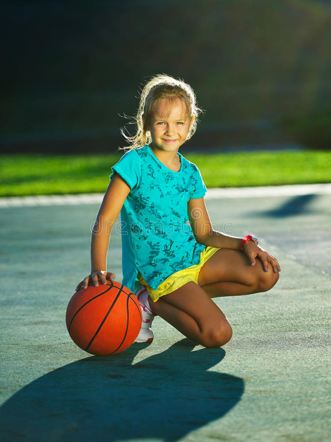 Photo of little cute girl playing basketball outdoors royalty free stock photo