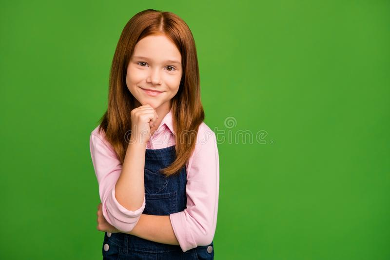 Photo of little ginger schoolchild in front of blackboard hand on chin listening teacher absorb knowledge like rubber. Wear denim overall pink, shirt isolated royalty free stock image