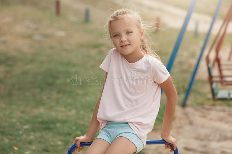 Photo of little girl on playground, spending time with friends and playing outdoors in summer. Happy kid in kindergarten or stock photography
