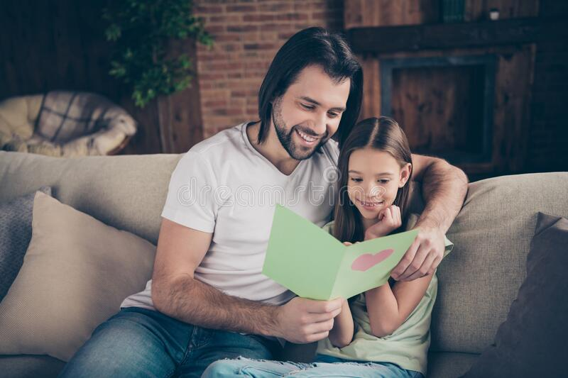 Photo of little pretty funny lady her handsome daddy sit cozy sofa hugging hold cute card birthday present reading. Photo of little pretty funny lady her stock images