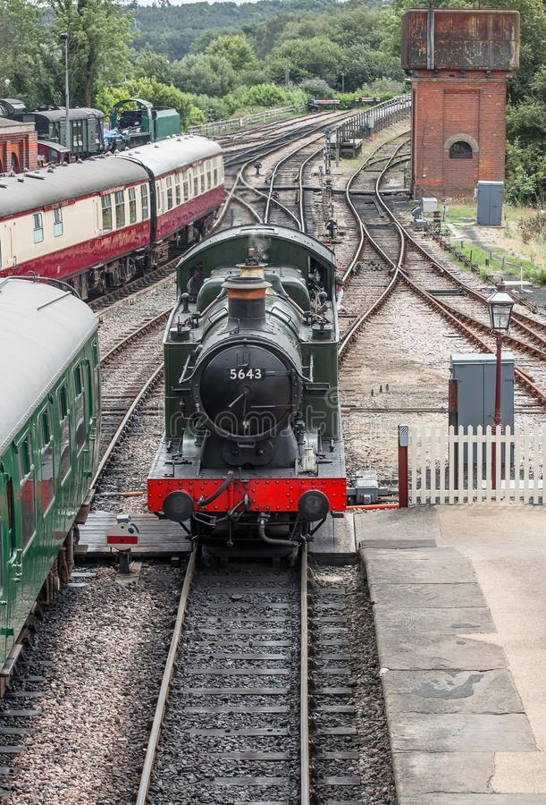A 0.6.0 locomotive shunting. Photo of a 0.6.0 locomotive shunting past carriages in a station stock photography
