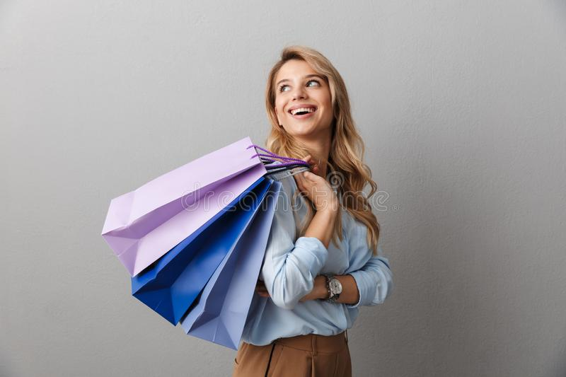 Photo of lovely elegant woman with long curly hair smiling and carrying colorful shopping bags. Isolated over gray background stock images