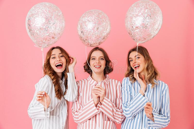 Photo of lovely teen girls 20s in colorful striped pyjamas holding air balloons and smiling on camera at slumber party, isolated stock image