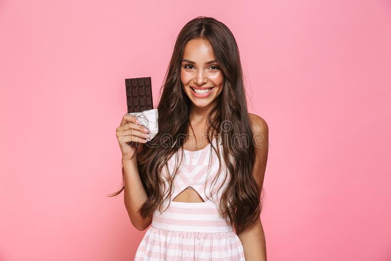 Photo of lovely woman 20s wearing dress smiling and eating chocolate bar, isolated over pink background stock photo