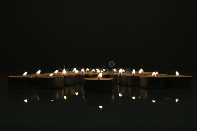 Candles burning in the dark. Tealight candles in the darkness. Photo of low-burning tealight candles standing on a transparent table. Dark background, romantic stock photo