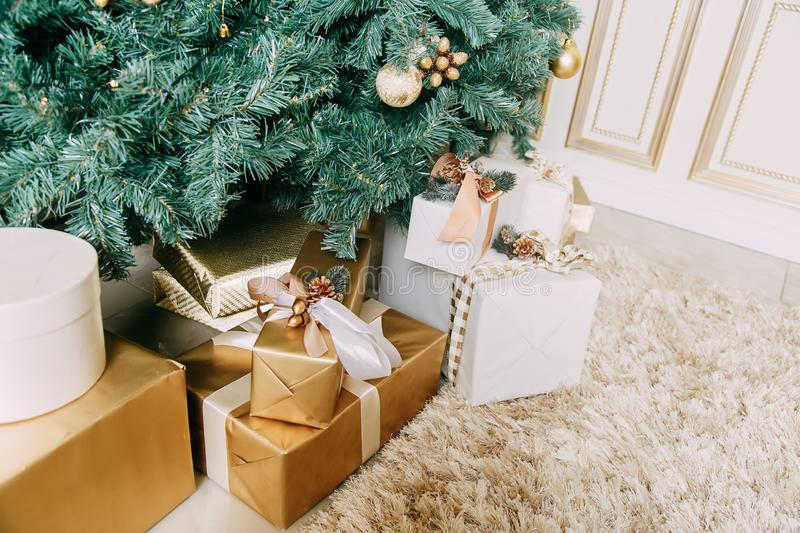 Photo of luxury gift boxes under Christmas tree, New Year home decorations, golden wrapping of Santa presents stock images