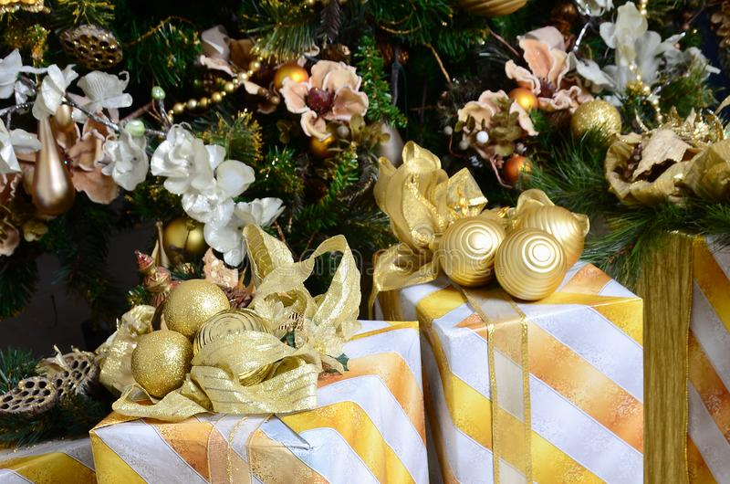Photo of luxury gift boxes under Christmas tree, New Year home decorations, golden wrapping of Santa presents, festive fir tree de royalty free stock photos