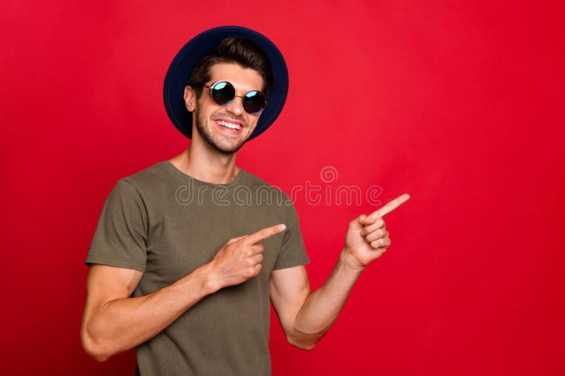 Photo of macho guy indicating fingers empty space wear vintage hat sun specs and grey t-shirt isolated on red background stock photography