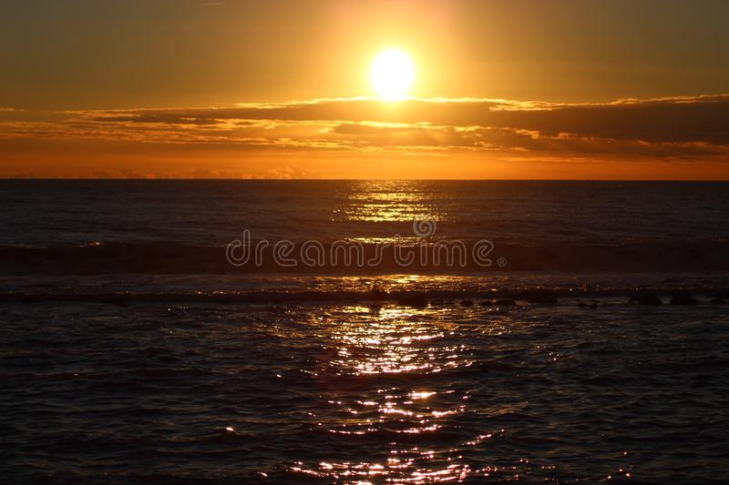 The sunset at the beach in Italy. This photo is made in Marina di Massa, Italy during the sunset. you can see the beautiful colors. yellow, orange a bit red royalty free stock image