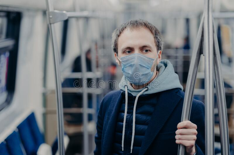 Photo of male passenger wears face mask while travels by subway during infectious disease, prevents spreading coronavirus, poses. In public transport, thinks royalty free stock images