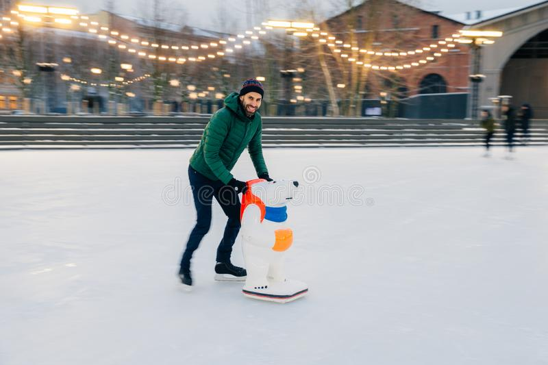 Photo of male skater keeps balance on skate ring, stands on skates with help of skate aid, spends winter weekends with fun, enjoy royalty free stock photography