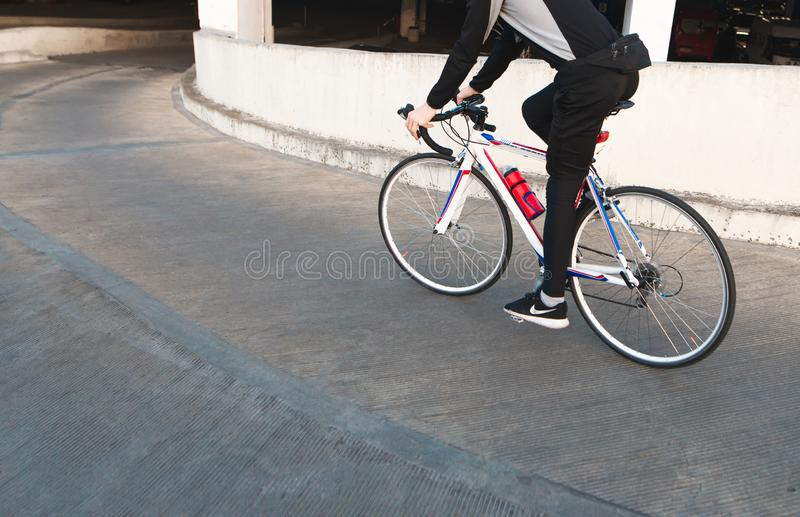 Photo of a man in dark sporty clothes riding a bridge on a bike. Rider rides a bike, looks from the back stock photography