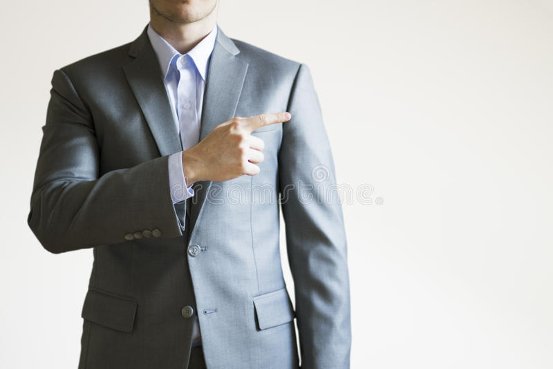 Photo of a man in grey suit pointing at empty space next to him royalty free stock photos