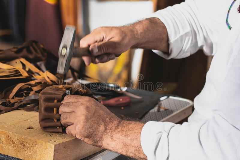 Man with hammer in hand working on leather sandals, homemade concept. Photo of man with hammer in hand working on leather sandals, homemade concept royalty free stock photography