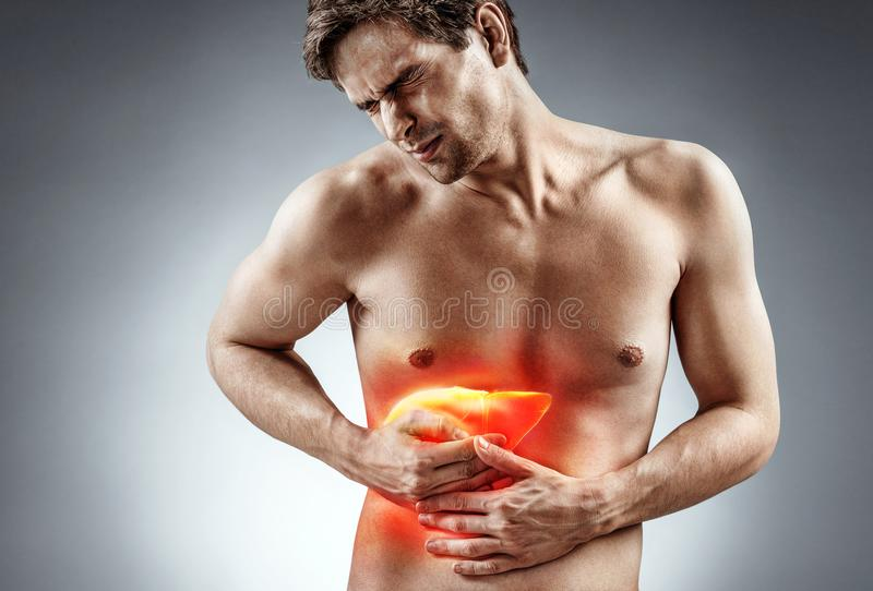 Photo of man holding his hand in area liver. Cirrhosis of the liver. Photo of man holding his hand in area liver and grimacing in pain on grey background royalty free stock image