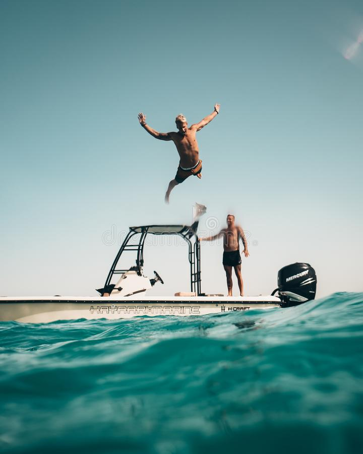 Photo of Man Jumping from Boat to the Sea royalty free stock photo
