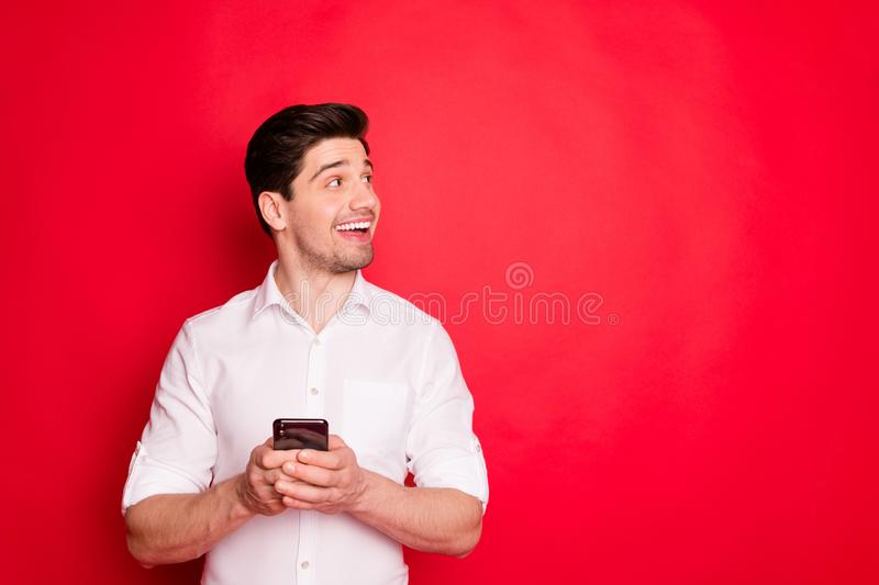 Photo of man looking at emptiness called copyspace in wait of its being fulfilled while isolated with red background. Photo of man looking at emptiness called stock photo