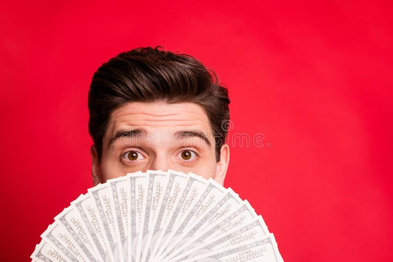 Photo of man looking out of money fan successful having received salary while isolated with red background. Photo of man looking out of money fan, successful stock image