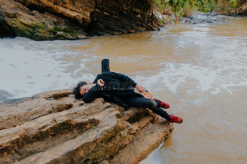 Photo of Man Lying on Rock at River royalty free stock image