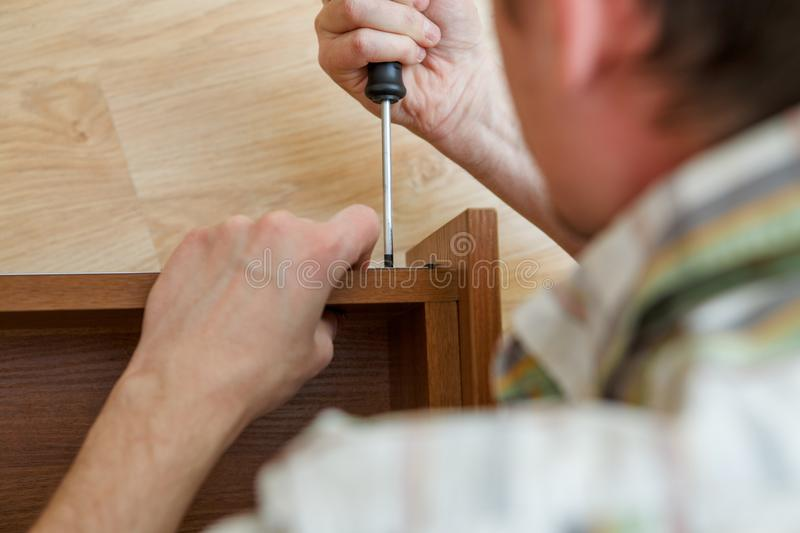 Photo of man with screwdriver picking box royalty free stock photos
