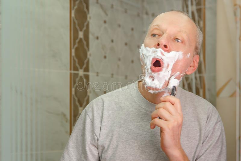 Photo of a man shaving his face royalty free stock image