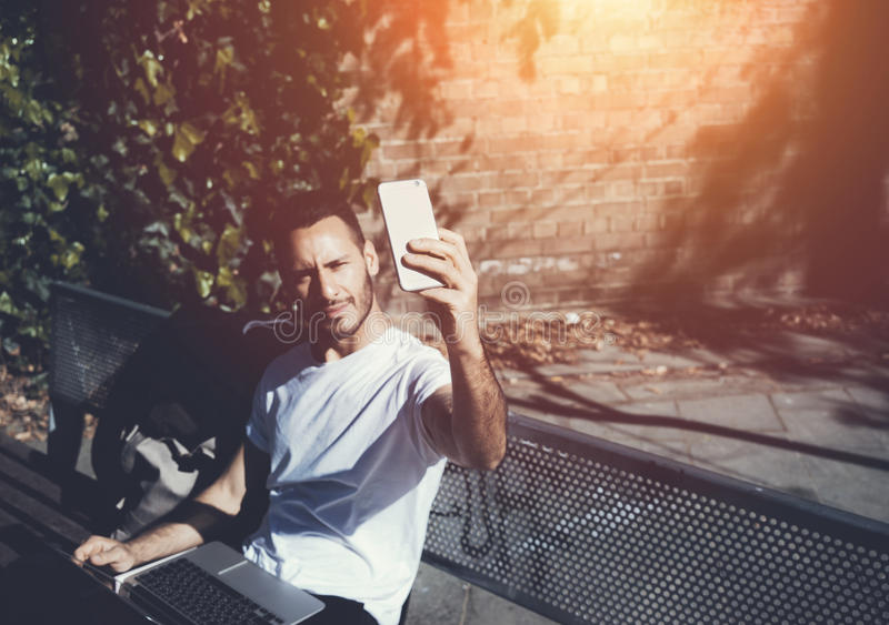 Photo man sitting city park bench and making selfie smartphone. Using wireless internet. Studying at the University stock photos