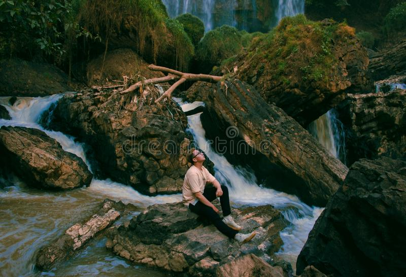 Photo of Man Sitting on Gray Rock Surrounded by Water Falls stock photo