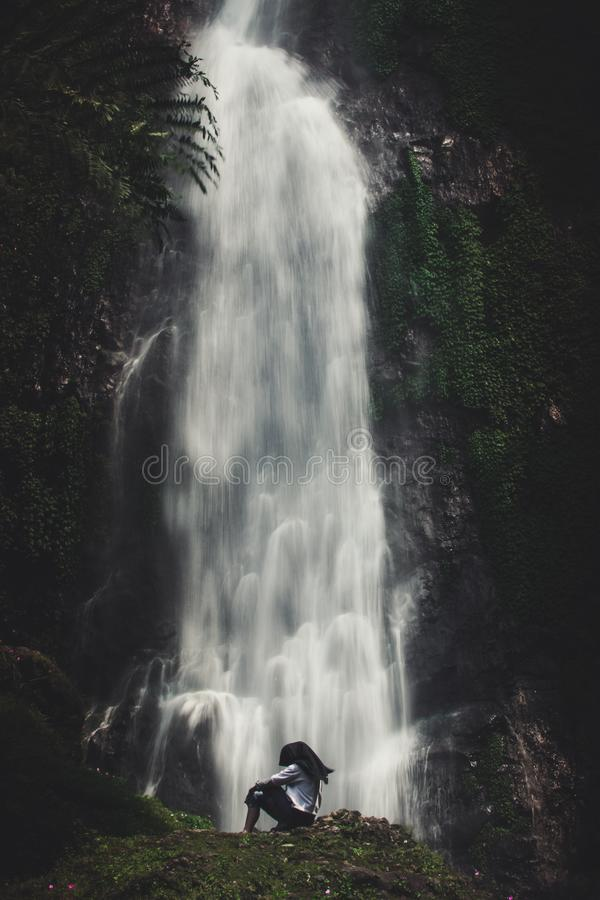 Photo of Man Sitting Near Waterfalls royalty free stock images