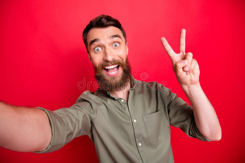Photo of man taking selfie showing you v-sign with his face astonished while  with red background. Photo of man taking selfie showing you v-sign with his face stock photos