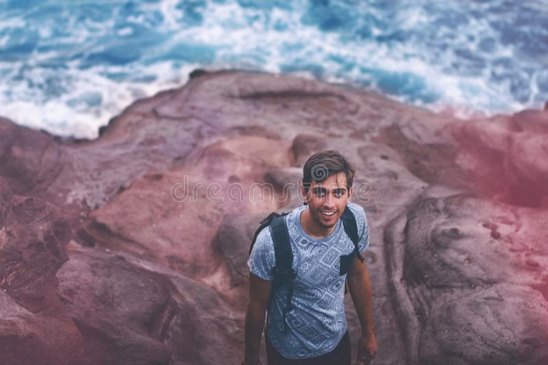 Photo Of Man Wearing Blue Shirt And Backpack Near Ocean stock photo