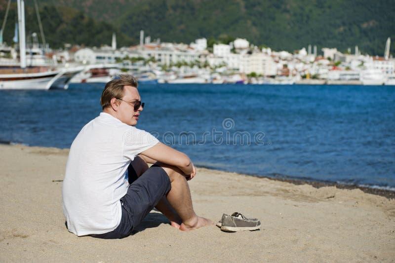 Photo of Man in White Shirt and Blue Short Sitting on Seashore stock photo