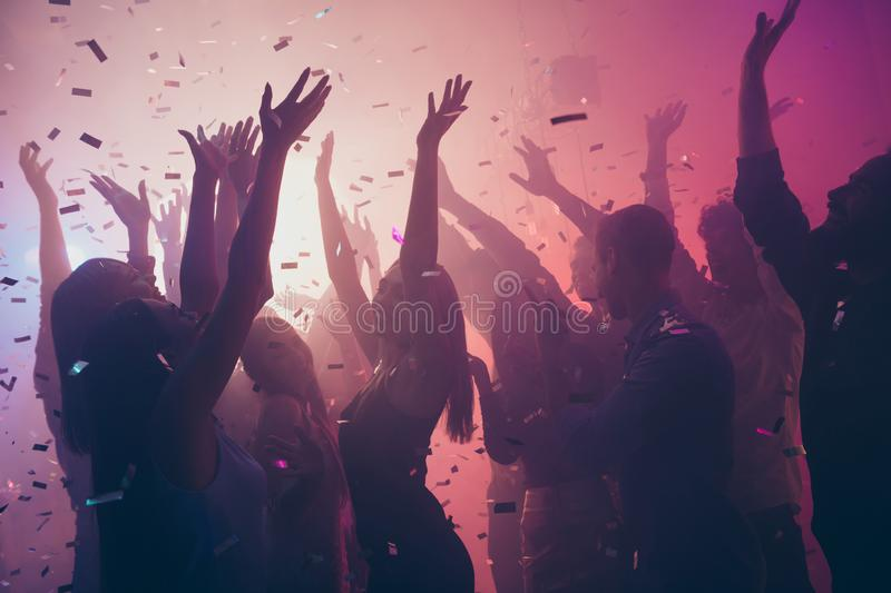 Photo of many birthday event people dancing colorful lights confetti flying enjoy nightclub hands raised up wear shiny. Photo of many birthday event people stock image