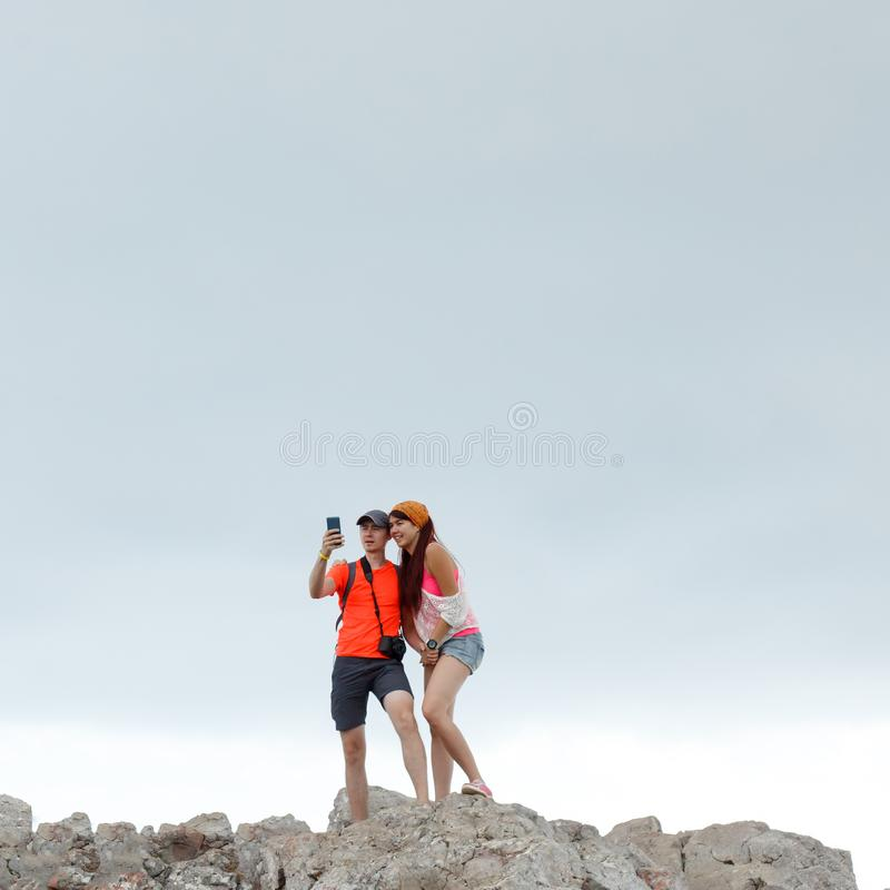 Photo of man and woman taking pictures of themselves while standing on mountain stock photo