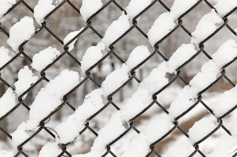 Metal grating covered snow. Photo of a metal grating covered with white snow falling during a snowfall, close up royalty free stock images