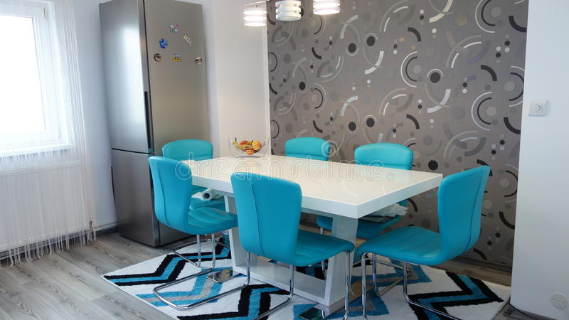 Photo of mid size kitchen apartment in turquoise colours, leather modern and minimalist seater, white dining table for six persons. Photo session of mid size royalty free stock photo