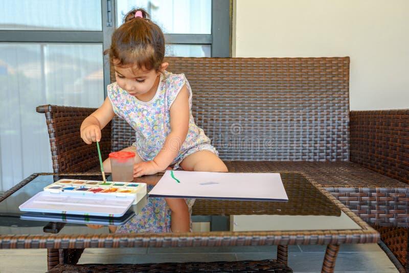 Photo mignonne de peinture de petite fille sur le fond int?rieur ? la maison Gar?on et filles s'asseyant sur le bureau surfant et image stock