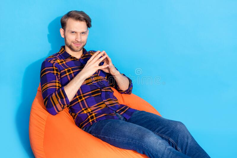 Photo of minded happy young man hold hands together evil genius sit bean bag  on blue color background.  royalty free stock photo