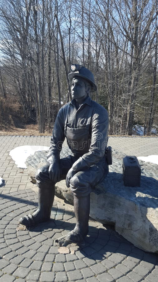 A photo of a miner sitting down either taking a break or eating his lunch. A photo of a memorial of the miners that started Elliot Lake Canada ontario by mining royalty free stock photos