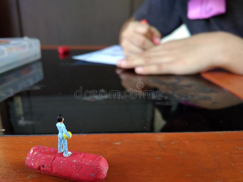 Mini Figure Boy standing at crayon, waiting for his friend coloring to play soccer royalty free stock photography