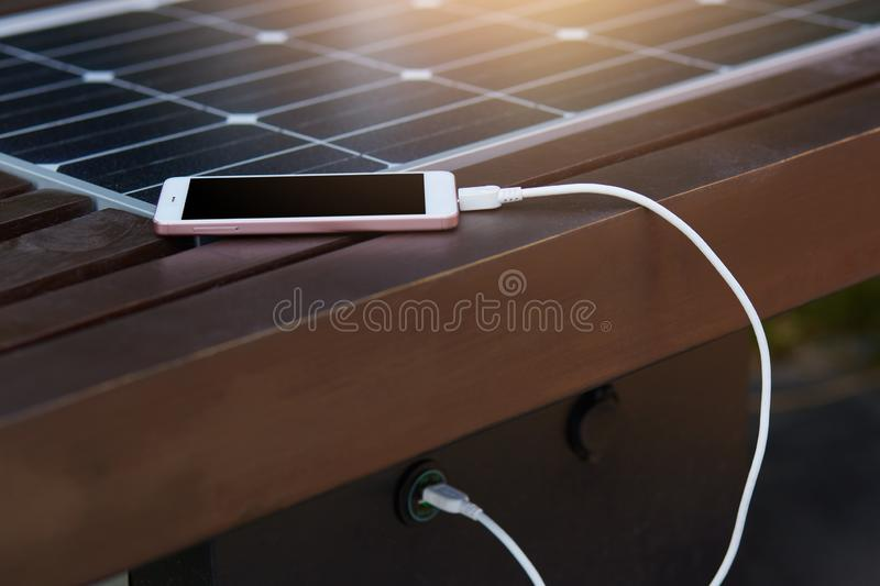 Photo of mobile phone charging via USB from solar power on bench on town street. Alternative electricity source, ecology,. Sustainable resources, renewable royalty free stock photography