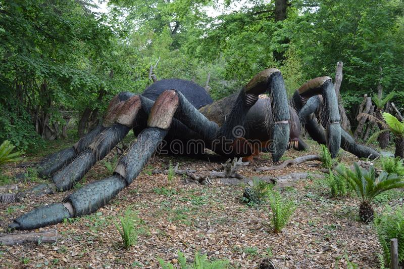 Model of big black spider standing in park. Photo of model of big black spider standing in park, long lags, green grass and trees royalty free stock images