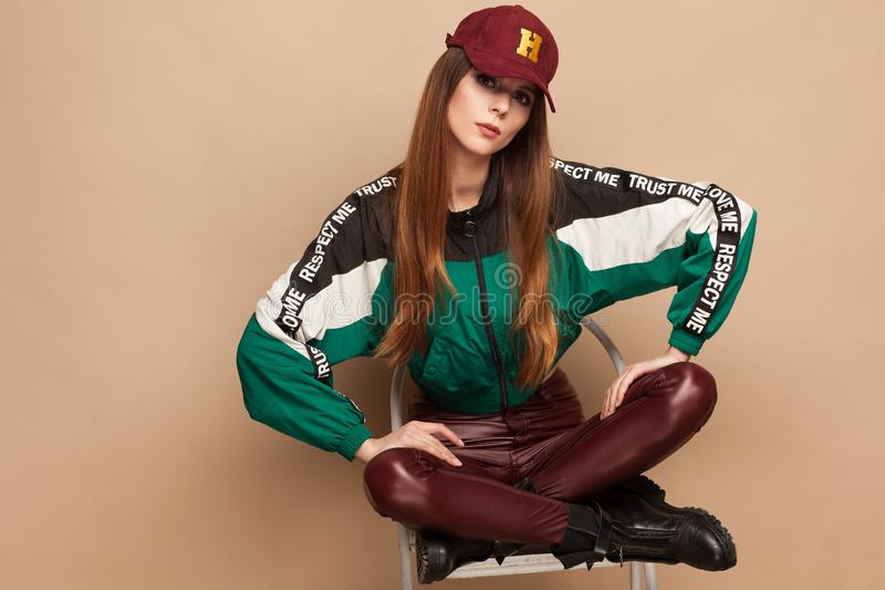Photo of the model, wearing a jacket, cap and brown stretch jeans. Beige background stock photo