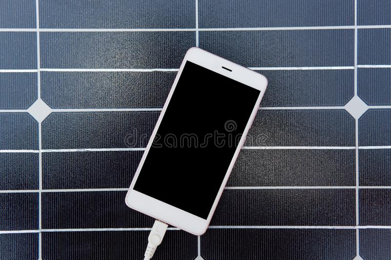 Photo of modern device charging via USB, lying on solar power panel, top view of smartphone with white cabel connected to it over. Dark background, sustainable stock images
