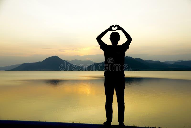 Photo modifiée la tonalité des mains dans la forme de coeur sur le fond de ciel photographie stock libre de droits