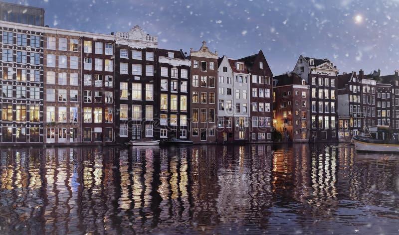 Photo modifiée la tonalité des maisons de danse célèbres du canal de Damrak à Amsterdam la nuit d'hiver image libre de droits