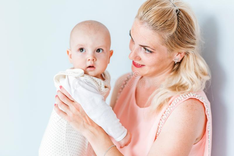 Mom in a pink dress holds her little son in her arms and smiles. Photo of mom in a pink dress holds her little son in her arms and smiles stock photography